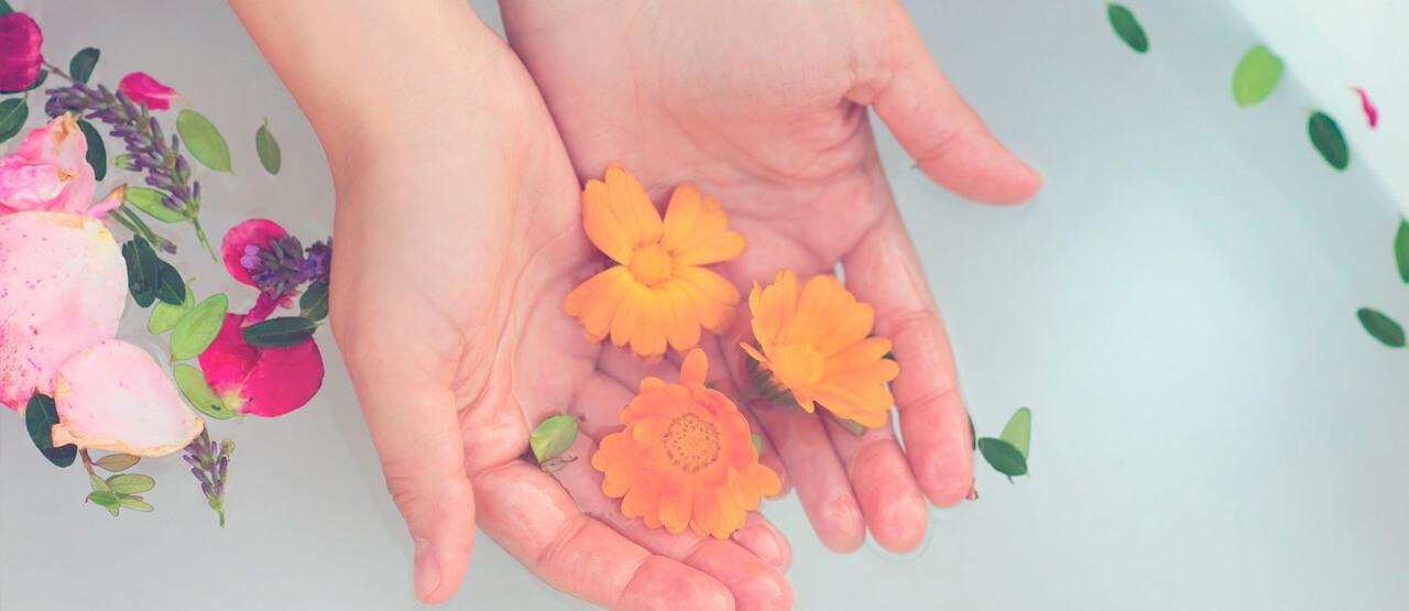 Manos y bañera con pétalos de flores relajante